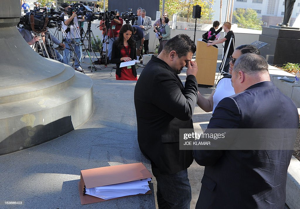 Michael Duran (C), who received nearly one million USD in a sex abuse settlement with the Roman Catholic Archdiocese of Los Angeles, gets ready to speak at a news conference on March 14, 2013 in Los Angeles, California. Duran wants Pope Francis to defrock Cardinal Roger Mahony over his role in the cover up. Duran is one of four men who reached a nearly $10 million settlement against the Los Angeles Archdiocese, Mahony, and ex-priest Michael Baker, who is in jail after pleading guilty pleaded to a dozen sex charges. AFP PHOTO/JOE KLAMAR