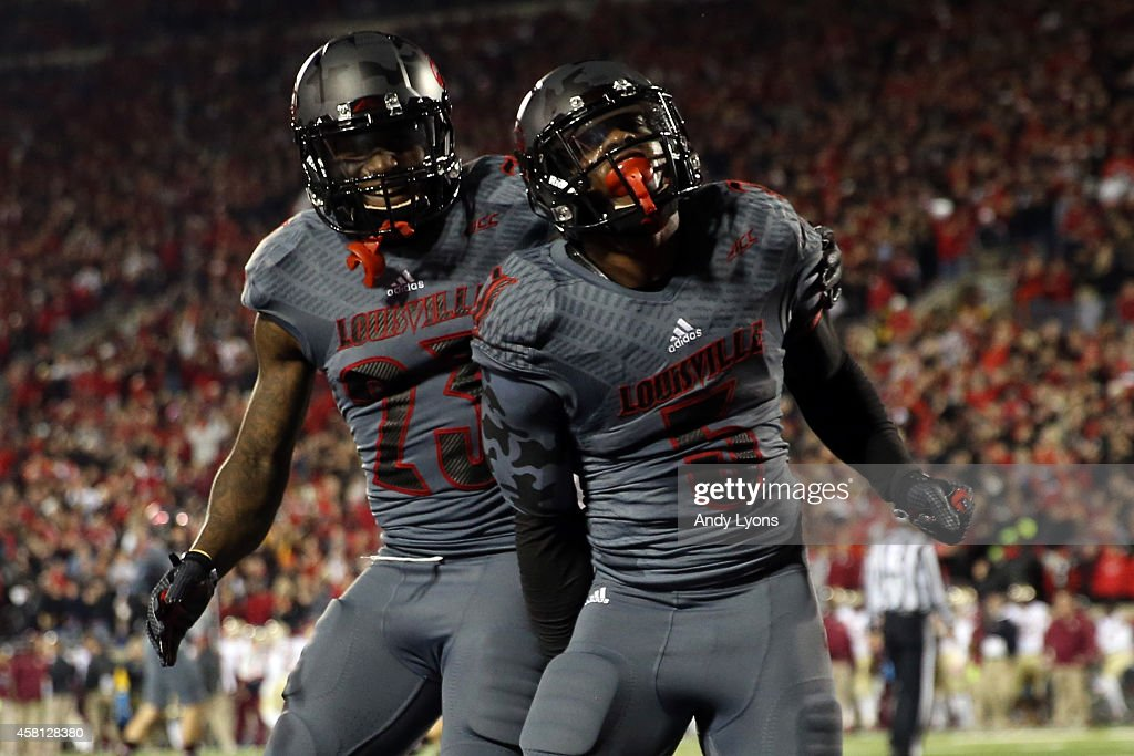 Michael Dyer of the Louisville Cardinals celebrates with teammate Brandon Radcliff after running a 4 yard touchdown in the second quarter against the...