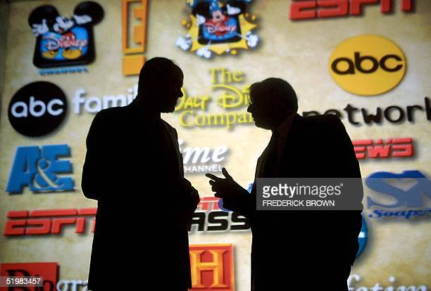 Michael Eisner chairman and CEO of the Walt Disney Company talks with Mel Woods president and CEO of the Haim Saban in front of a projection showing...
