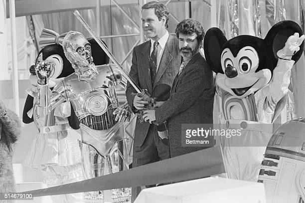 Michael Eisner chairman of Disney and film director George Lucas take part in a ribbon cutting ceremony for the new Star Tours ride in Disneyland...