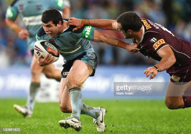 Michael Ennis of the Blues is tackled during game one of the ARL State of Origin series between the New South Wales Blues and the Queensland Maroons...