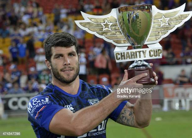 Michael Ennis of the Bulldogs holds up the inaugural Charity Cup winners trophy during the NRL trial match between the Melbourne Storm and the...
