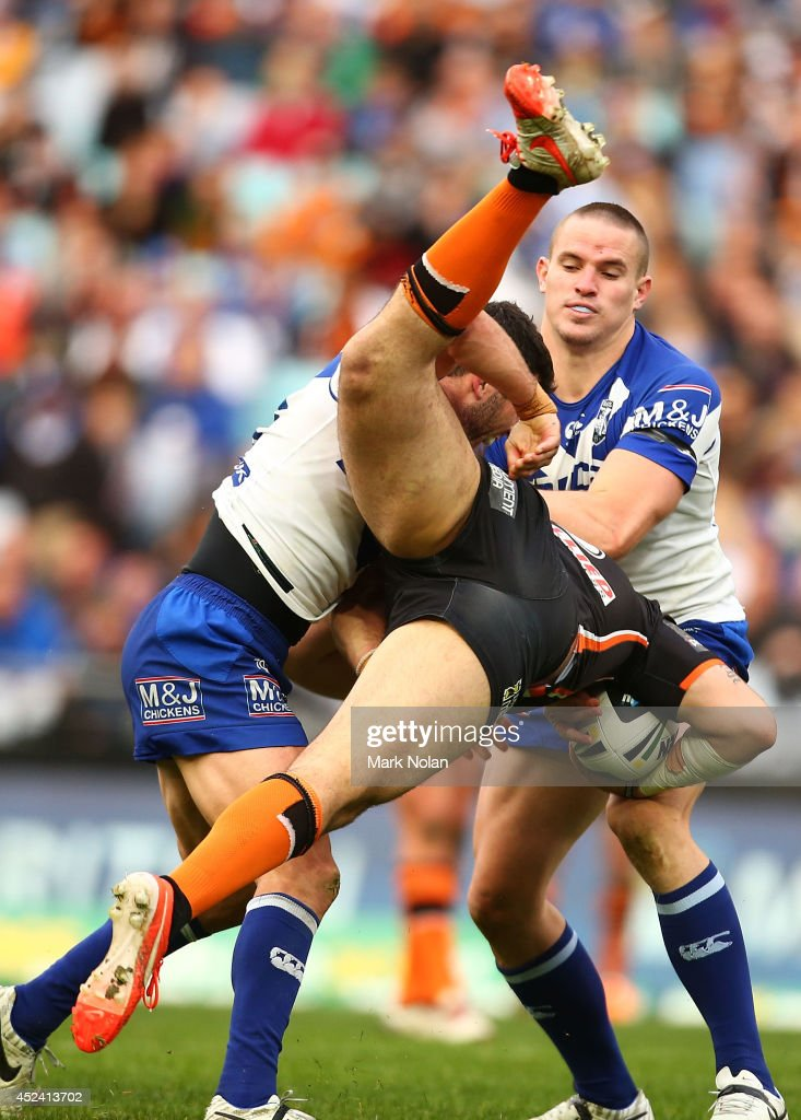 Michael Ennis of the Bulldogs up ends Aaron Woods of the Tigers during the round 19 NRL match between the Wests Tigers and the Canterbury Bulldogs at ANZ Stadium on July 20, 2014 in Sydney, Australia.
