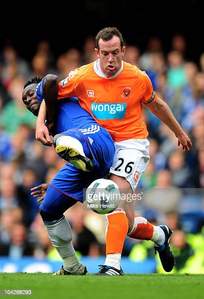 Michael Essien of Chelsea and Charlie Adam of Blackpool compete for the ball during the Barclays Premier League match between Chelsea and Blackpool...