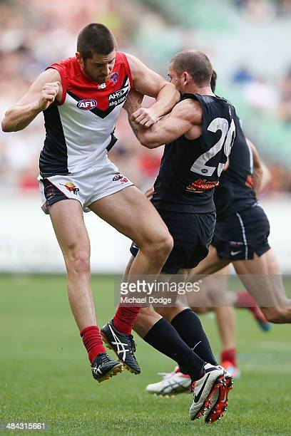 Michael Evans of the Demons bumps Heath Scotland of the Blues during the round four AFL match between the Carlton Blues and the Melbourne Demons at...