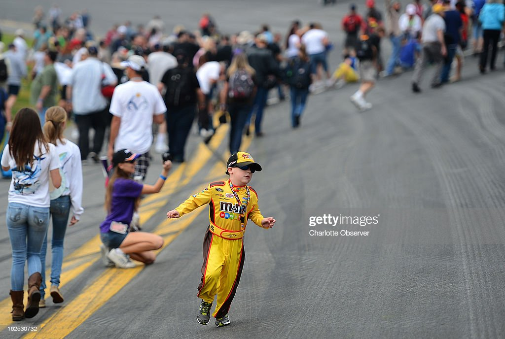 Michael Farmer, 7, of West Palm Beach, Florida, runs along the frontstretch of Daytona International Speedway, as fans mingle and walk up the banking of the track in Daytona Beach, Florida, Sunday, February 24, 2013.