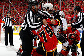 Michael Ferland of the Calgary Flames and Ryan Palmieri of the Anaheim Ducks are pulled apart by a referee at Scotiabank Saddledome for Game Four of...