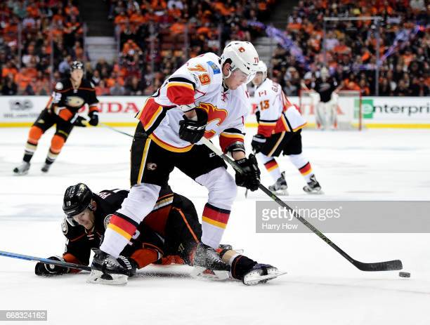 Michael Ferland of the Calgary Flames clears the puck from Corey Perry of the Anaheim Ducks during a 32 Ducks win in Game One of the Western...