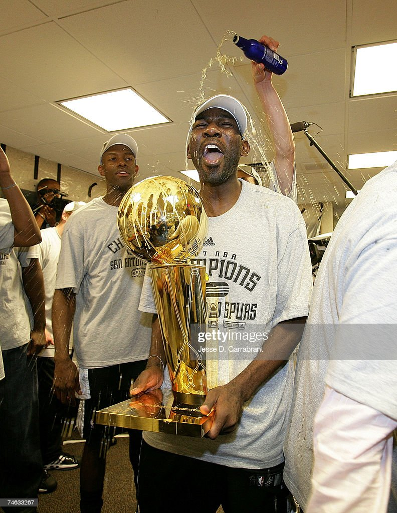 Michael Finley #4 of the San Antonio Spurs celebrates in the locker room with the Larry O'Brian Trophy after their 83-82 win against the Cleveland Cavaliers in Game Four of the NBA Finals at the Quicken Loans Arena on June 14, 2007 in Cleveland, Ohio.