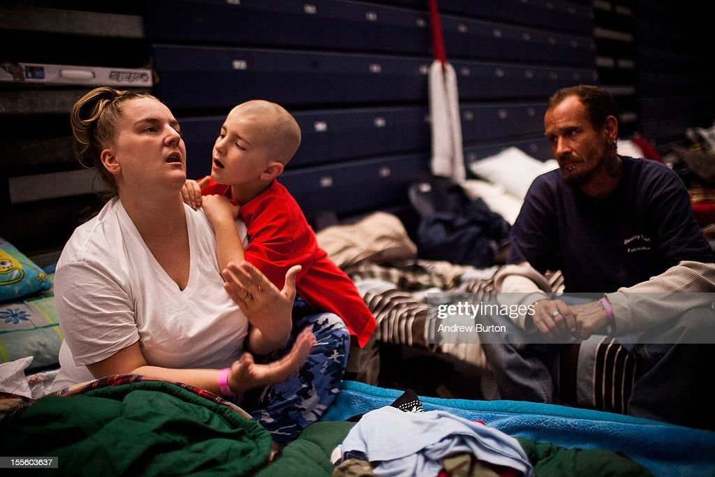 Michael Fischkelta, age 8, leans on his mother, Jenifer Wilson, in a Red Cross evacuation shelter set up in the gymnasium of Toms River High School on November 5, 2012 in Toms River, NJ, United States. This shelter has been open since October 28 - one day before Superstorm Sandy landed in New Jersey- though those still in need of assistance will be moved to new evacuation centers sometime this week, as the high school reopens for classes on Thursday.