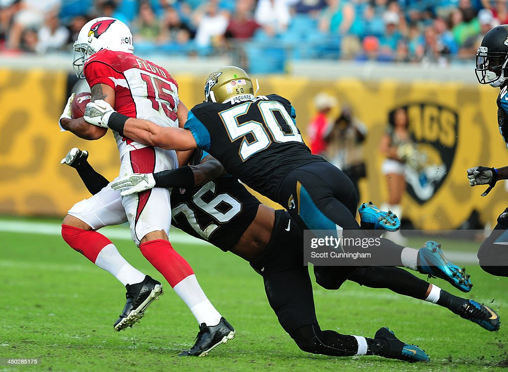 Michael Floyd #15 of the Arizona Cardinals runs with a catch for a touchdown against Russell Allen #50 and Josh Evans #26 of the Jacksonville Jaguars at EverBank Field on November 17, 2013 in Jacksonville, Florida.