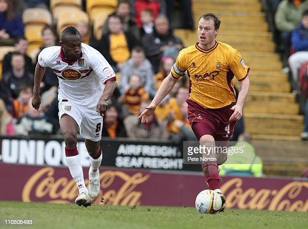 Michael Flynn of Bradford City moves forward with the ball watched by Abdul Osman of Northampton Town during the npower League Two match between...