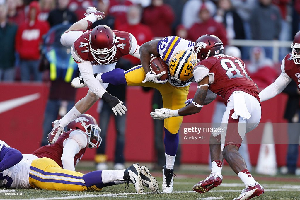 Michael Ford #42 of the LSU Tigers is tackled by Cameron Bryan #47 and Demetrius Wilson #81 of the Arkansas Razorbacks at Razorback Stadium on November 23, 2012 in Fayetteville, Arkansas. The Tigers defeated the Razorbacks 20-13.