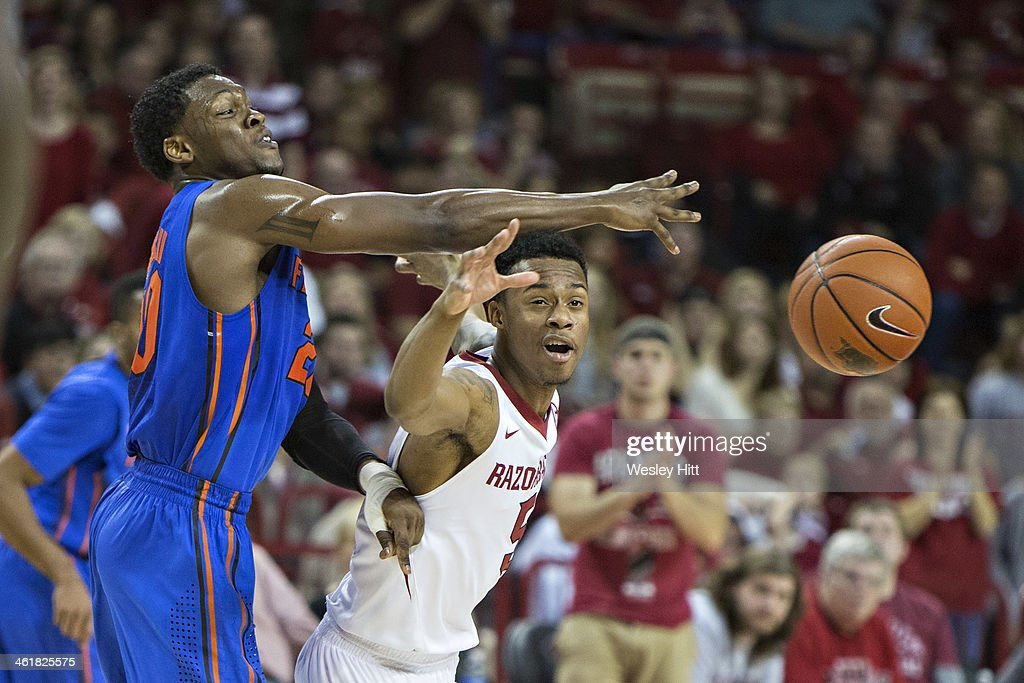Michael Frazier II #20 of the Florida Gators is fouled by Anthlon Bell #5 of the Arkansas Razorbacks at Bud Walton Arena on January 11, 2014 in Fayetteville, Arkansas. The Gators defeated the Razorbacks 84-82.