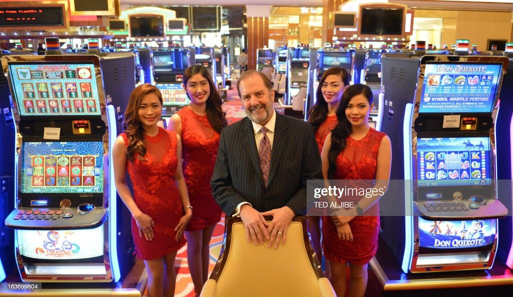 Michael French (C), chief operating officer of Solaire Resorts and casino, poses for photo next to gaming machines inside the casino in Manila on March 14, 2013, ahead of its opening on March 16. The Philippines makes its biggest bet this weekend in a high-stakes bid to join the world's elite gaming destinations, with the launch of a $1.2-billion casino on Manila Bay.Solaire Manila Resorts is the first of four enormous entertainment venues slated to rise over a giant chunk of prime, reclaimed land that industry and government leaders expect will attract millions of cashed-up Asian tourists.