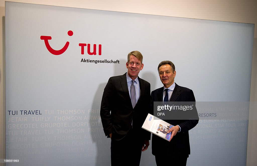 Michael Frenzel (R), outgoing chairman of German tourism giant TUI, and his successor Friedrich Joussen pose in front of their company's logo on the sidelines of a press conference in Hanover, central Germany, on December 19, 2012. TUI posted a net loss for the 2012 financial year due to difficulties at shipping company Hapag Lloyd in which it holds a stake.