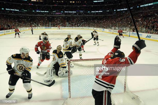 Michael Frolik of the Chicago Blackhawks celebrates after teammate Johnny Oduya scored a goal in the third period against goalie Tuukka Rask of the...
