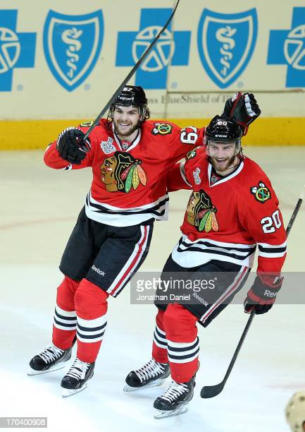 Michael Frolik and Brandon Saad of the Chicago Blackhawks celebrate after Johnny Oduya scored a goal in the third period against the Boston Bruins in...
