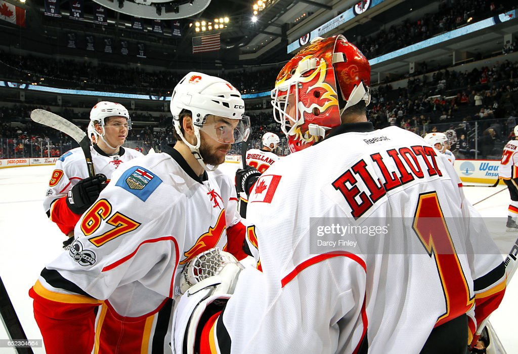 Michael Frolik #67 and goaltender Brian Elliott #1 of the Calgary Flames celebrate a 3-0 victory over the Winnipeg Jets at the MTS Centre on March 11, 2017 in Winnipeg, Manitoba, Canada.