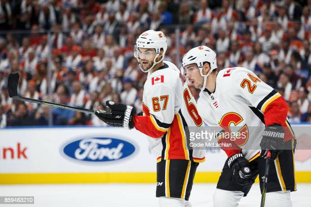 Michael Frolik and Travis Hamonic of the Calgary Flames strategize against the Edmonton Oilers at Rogers Place on October 4 2017 in Edmonton Canada