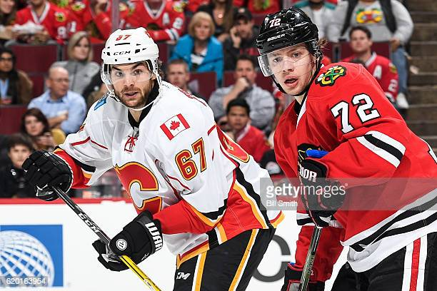 Michael Frolik of the Calgary Flames and Artemi Panarin of the Chicago Blackhawks watch for the puck in the first period at the United Center on...