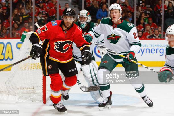 Michael Frolik of the Calgary Flames and Gustav Olofsson of the Minnesota Wild look for a pass in an NHL game against the Minnesota Wild at the...