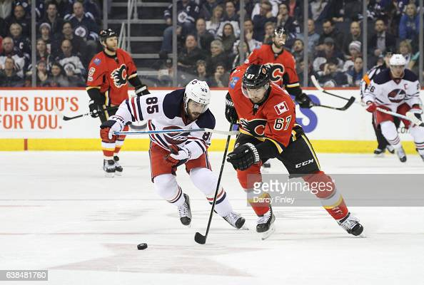 Michael Frolik of the Calgary Flames and Mathieu Perreault of the Winnipeg Jets chase the loose puck down the ice during third period action at the...