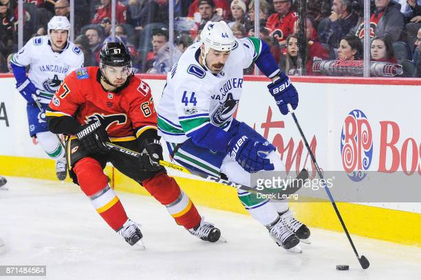 Michael Frolik of the Calgary Flames chases the puck against Erik Gudbranson of the Vancouver Canucks during an NHL game at Scotiabank Saddledome on...