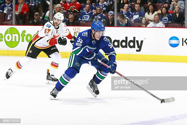 Michael Frolik of the Calgary Flames looks on as Bo Horvat of the Vancouver Canucks skates up ice with the puck during their NHL game at Rogers Arena...