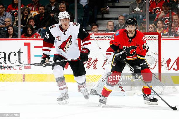 Michael Frolik of the Calgary Flames skates against Michael Stone of the Arizona Coyotes during an NHL game on November 16 2016 at the Scotiabank...