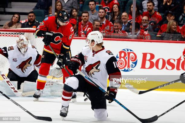 Michael Frolik of the Calgary Flames tries to tip a shot past Mike Smith of the Arizona Coyotes during an NHL game on February 13 2017 at the...