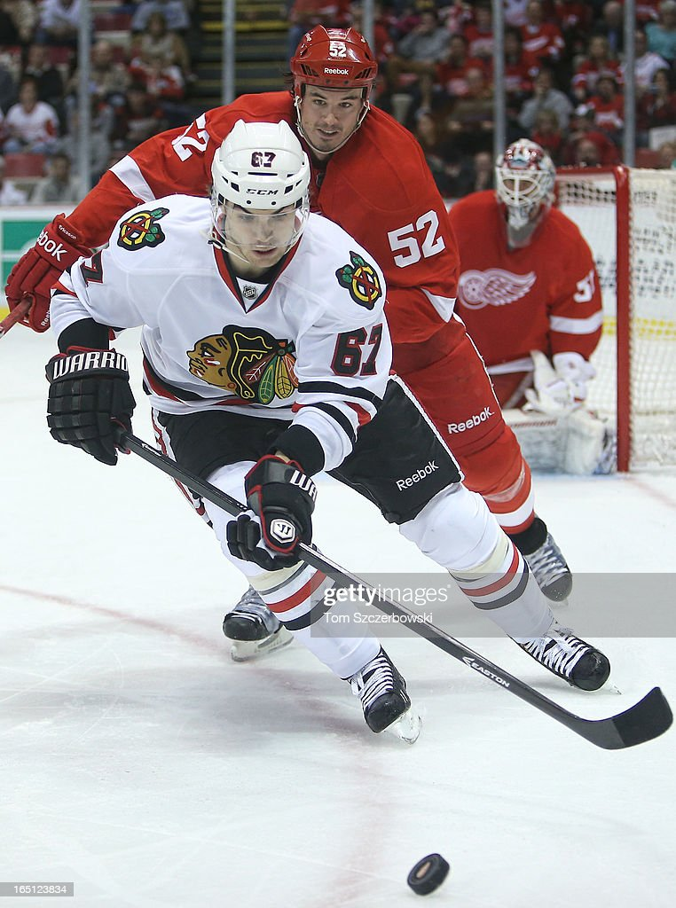 <a gi-track='captionPersonalityLinkClicked' href=/galleries/search?phrase=Michael+Frolik&family=editorial&specificpeople=537965 ng-click='$event.stopPropagation()'>Michael Frolik</a> #67 of the Chicago Blackhawks picks up the puck during an NHL game as <a gi-track='captionPersonalityLinkClicked' href=/galleries/search?phrase=Jonathan+Ericsson&family=editorial&specificpeople=2538498 ng-click='$event.stopPropagation()'>Jonathan Ericsson</a> #52 of the Detroit Red Wings backchecks at Joe Louis Arena on March 31, 2013 in Detroit, Michigan.