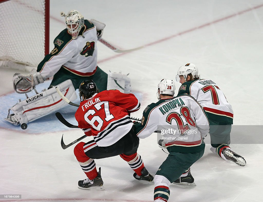 <a gi-track='captionPersonalityLinkClicked' href=/galleries/search?phrase=Michael+Frolik&family=editorial&specificpeople=537965 ng-click='$event.stopPropagation()'>Michael Frolik</a> #67 of the Chicago Blackhawks scores a goal against <a gi-track='captionPersonalityLinkClicked' href=/galleries/search?phrase=Josh+Harding&family=editorial&specificpeople=700587 ng-click='$event.stopPropagation()'>Josh Harding</a> #37, <a gi-track='captionPersonalityLinkClicked' href=/galleries/search?phrase=Zenon+Konopka&family=editorial&specificpeople=2105876 ng-click='$event.stopPropagation()'>Zenon Konopka</a> #28 and <a gi-track='captionPersonalityLinkClicked' href=/galleries/search?phrase=Tom+Gilbert&family=editorial&specificpeople=687083 ng-click='$event.stopPropagation()'>Tom Gilbert</a> #77 of the Minnesota Wild in Game Two of the Western Conference Quarterfinals during the 2013 NHL Stanley Cup Playoffs at the United Center on May 3, 2013 in Chicago, Illinois.