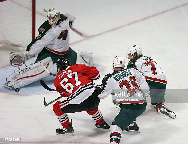 Michael Frolik of the Chicago Blackhawks scores a goal against Josh Harding Zenon Konopka and Tom Gilbert of the Minnesota Wild in Game Two of the...
