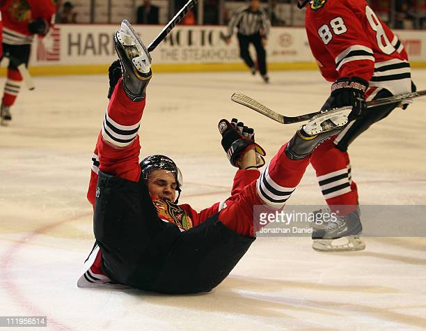 Michael Frolik of the Chicago Blackhawks slides across the ice after scoring a goal in the 2nd period against the Detroit Red Wings at the United...