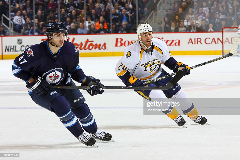 Michael Frolik #67 of the Winnipeg Jets and Eric Nystrom #24 of the Nashville Predators keep an eye on the play during first period action at the MTS Centre on November 8, 2013 in Winnipeg, Manitoba, Canada. The Jets defeated the Preds 5-0.