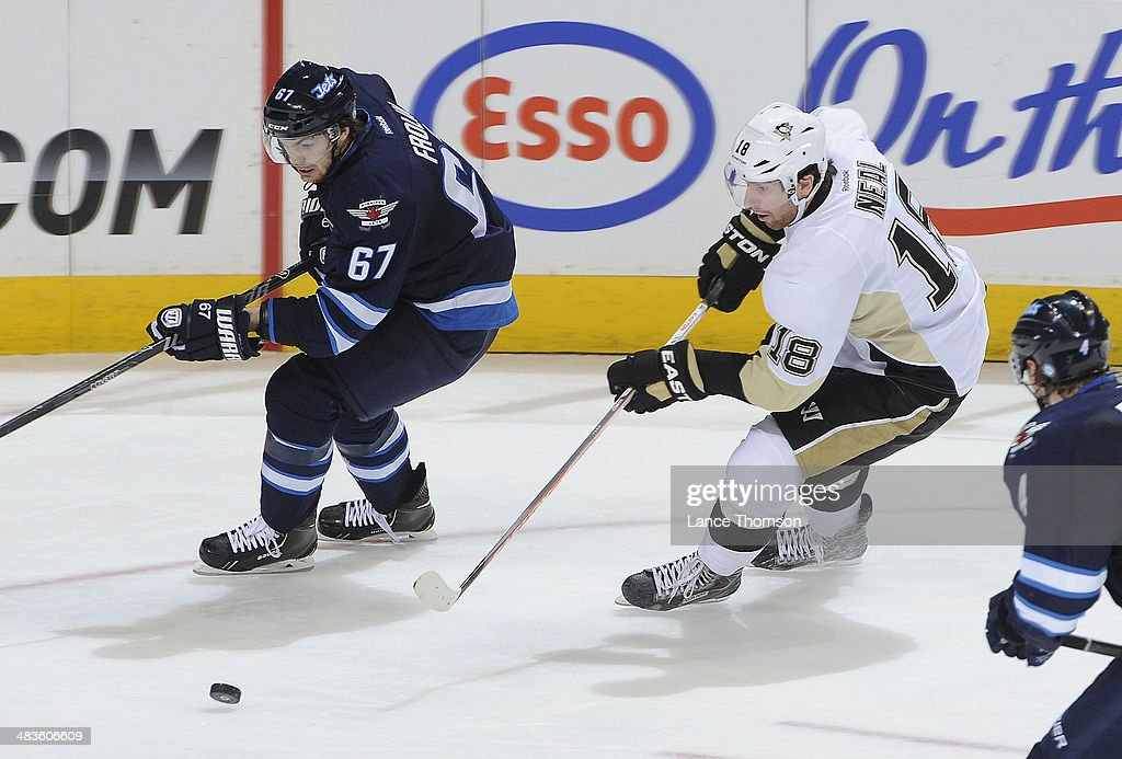 <a gi-track='captionPersonalityLinkClicked' href=/galleries/search?phrase=Michael+Frolik&family=editorial&specificpeople=537965 ng-click='$event.stopPropagation()'>Michael Frolik</a> #67 of the Winnipeg Jets and <a gi-track='captionPersonalityLinkClicked' href=/galleries/search?phrase=James+Neal&family=editorial&specificpeople=1487991 ng-click='$event.stopPropagation()'>James Neal</a> #18 of the Pittsburgh Penguins chase after the loose puck during second period action at the MTS Centre on April 3, 2014 in Winnipeg, Manitoba, Canada. The Pens defeated the Jets 4-2.