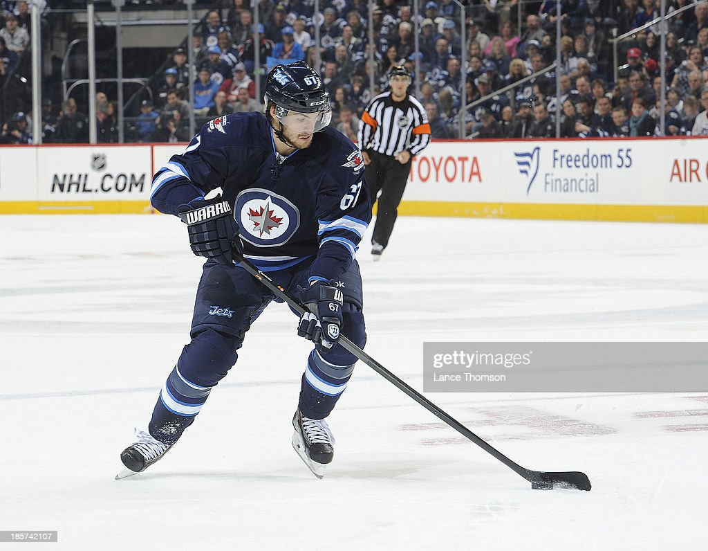 Michael Frolik #67 of the Winnipeg Jets carries the puck up the ice during first period action against the St. Louis Blues at the MTS Centre on October 18, 2013 in Winnipeg, Manitoba, Canada. The Jets defeated the Blues 4-3 in a shootout.
