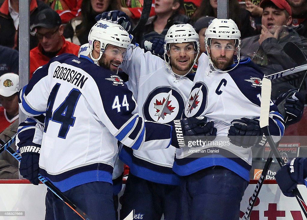 <a gi-track='captionPersonalityLinkClicked' href=/galleries/search?phrase=Michael+Frolik&family=editorial&specificpeople=537965 ng-click='$event.stopPropagation()'>Michael Frolik</a> #67 of the Winnipeg Jets celebrates his first period goal with <a gi-track='captionPersonalityLinkClicked' href=/galleries/search?phrase=Zach+Bogosian&family=editorial&specificpeople=4195061 ng-click='$event.stopPropagation()'>Zach Bogosian</a> #44 and <a gi-track='captionPersonalityLinkClicked' href=/galleries/search?phrase=Andrew+Ladd&family=editorial&specificpeople=228452 ng-click='$event.stopPropagation()'>Andrew Ladd</a> #16 against the Chicago Blackhawks at the United Center on November 2, 2014 in Chicago, Illinois.