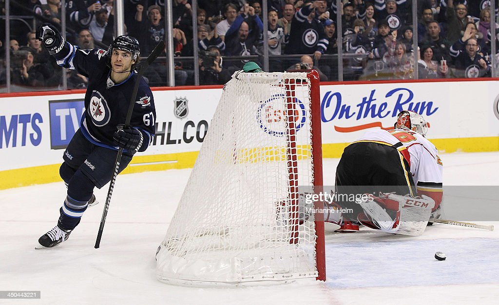 <a gi-track='captionPersonalityLinkClicked' href=/galleries/search?phrase=Michael+Frolik&family=editorial&specificpeople=537965 ng-click='$event.stopPropagation()'>Michael Frolik</a> #67 of the Winnipeg Jets celebrates his goal against Reto Berra #29 of the Calgary Flames in second period action in an NHL game at the MTS Centre on November 18, 2013 in Winnipeg, Manitoba, Canada.