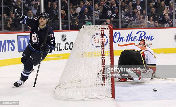 Michael Frolik of the Winnipeg Jets celebrates his goal against Reto Berra of the Calgary Flames in second period action in an NHL game at the MTS...
