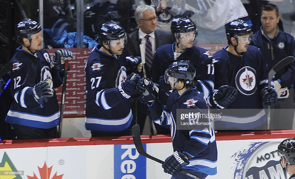 <a gi-track='captionPersonalityLinkClicked' href=/galleries/search?phrase=Michael+Frolik&family=editorial&specificpeople=537965 ng-click='$event.stopPropagation()'>Michael Frolik</a> #67 of the Winnipeg Jets gets congratulations from teammates at the bench after scoring a second period goal against the Minnesota Wild at the MTS Centre on November 23, 2013 in Winnipeg, Manitoba, Canada.