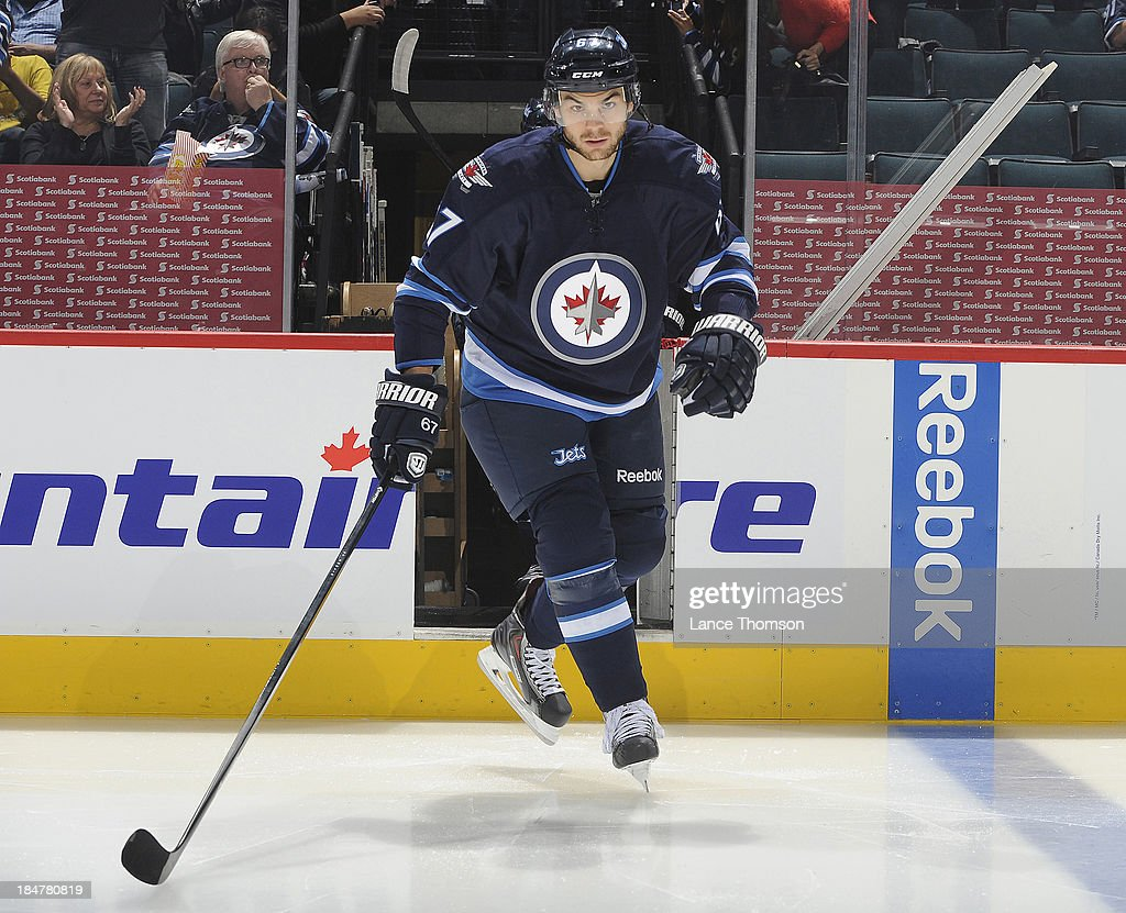 Michael Frolik #67 of the Winnipeg Jets hits the ice prior to puck drop against the Dallas Stars at the MTS Centre on October 11, 2013 in Winnipeg, Manitoba, Canada.