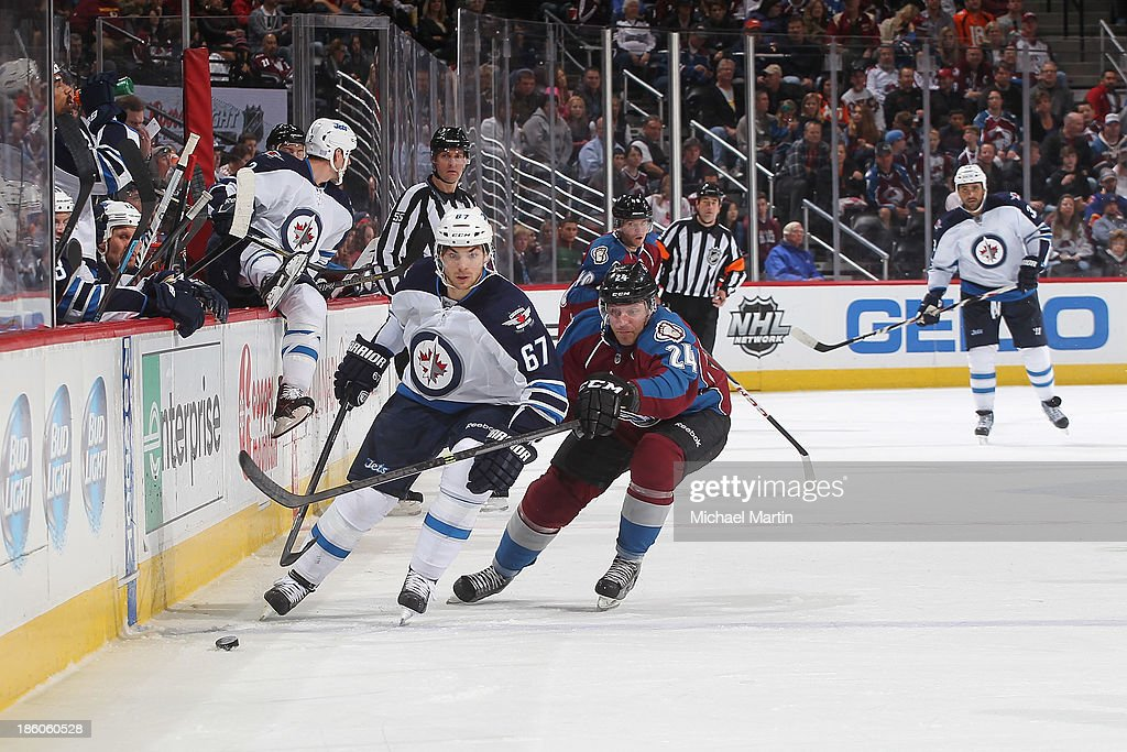 Michael Frolik #67 of the Winnipeg Jets is pursued by Marc-Andre Cliche #24 of the Colorado Avalanche at the Pepsi Center on October 27, 2013 in Denver, Colorado.