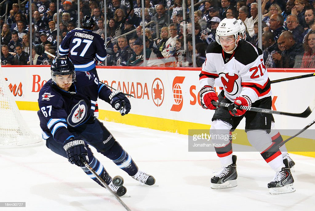 <a gi-track='captionPersonalityLinkClicked' href=/galleries/search?phrase=Michael+Frolik&family=editorial&specificpeople=537965 ng-click='$event.stopPropagation()'>Michael Frolik</a> #67 of the Winnipeg Jets plays the puck as <a gi-track='captionPersonalityLinkClicked' href=/galleries/search?phrase=Andrei+Loktionov&family=editorial&specificpeople=5370946 ng-click='$event.stopPropagation()'>Andrei Loktionov</a> #21 of the New Jersey Devils looks on during third period action at the MTS Centre on October 13, 2013 in Winnipeg, Manitoba, Canada.