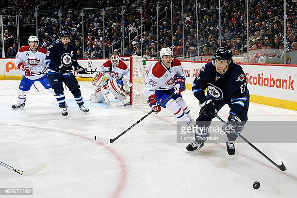 Michael Frolik of the Winnipeg Jets plays the puck as Jeff Petry of the Montreal Canadiens defends during first period action on March 26 2015 at the...