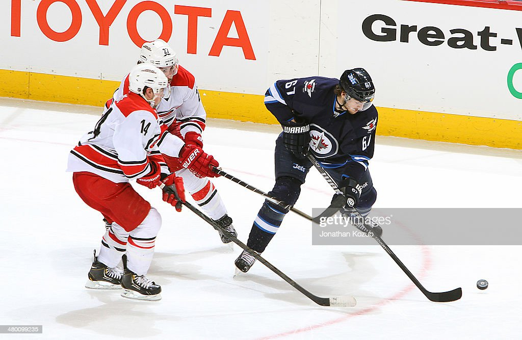 <a gi-track='captionPersonalityLinkClicked' href=/galleries/search?phrase=Michael+Frolik&family=editorial&specificpeople=537965 ng-click='$event.stopPropagation()'>Michael Frolik</a> #67 of the Winnipeg Jets plays the puck away from <a gi-track='captionPersonalityLinkClicked' href=/galleries/search?phrase=Nathan+Gerbe&family=editorial&specificpeople=697084 ng-click='$event.stopPropagation()'>Nathan Gerbe</a> #14 and Justin Faulk #27 of the Carolina Hurricanes during third period action at the MTS Centre on March 22, 2014 in Winnipeg, Manitoba, Canada.