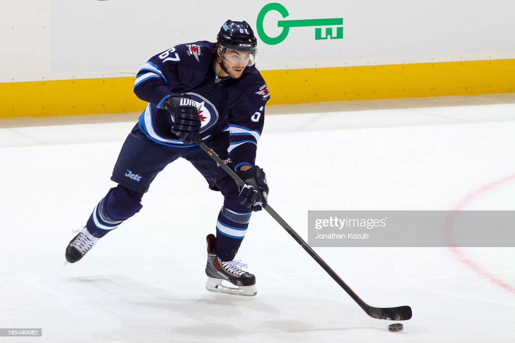 Michael Frolik #67 of the Winnipeg Jets plays the puck up the ice during second period action against the New Jersey Devils at the MTS Centre on October 13, 2013 in Winnipeg, Manitoba, Canada. The Jets defeated the Devils 3-0.