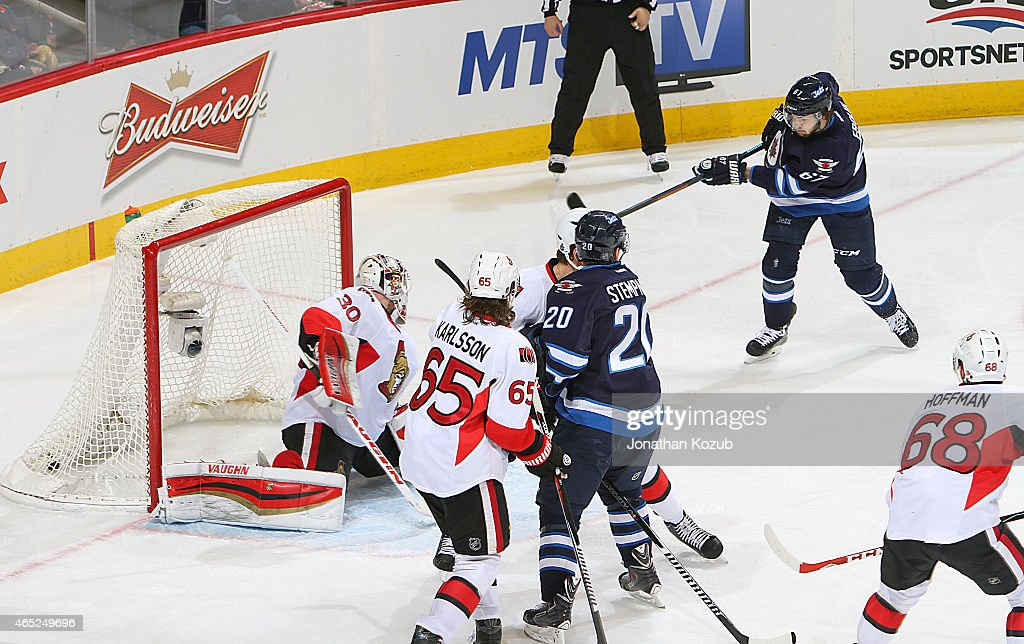 Michael Frolik #67 of the Winnipeg Jets shoots the puck into the net past goaltender Andrew Hammond #30 of the Ottawa Senators for a third period goal on March 4, 2015 at the MTS Centre in Winnipeg, Manitoba, Canada. (Photo by Jonathan Kozub/NHLI via Getty Images) *** Local Caption **Michael Frolik;Andrew Hammond