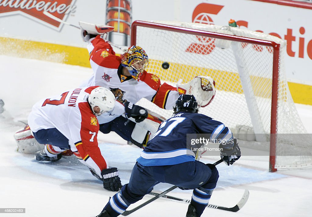 <a gi-track='captionPersonalityLinkClicked' href=/galleries/search?phrase=Michael+Frolik&family=editorial&specificpeople=537965 ng-click='$event.stopPropagation()'>Michael Frolik</a> #67 of the Winnipeg Jets shoots the puck over the shoulder of a diving goaltender <a gi-track='captionPersonalityLinkClicked' href=/galleries/search?phrase=Jacob+Markstrom&family=editorial&specificpeople=5370948 ng-click='$event.stopPropagation()'>Jacob Markstrom</a> #25 of the Florida Panthers during second period action at the MTS Centre on December 20, 2013 in Winnipeg, Manitoba, Canada.